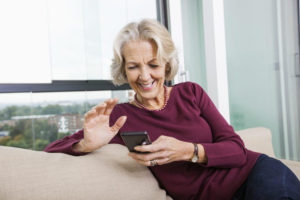 senior woman using mart phone on sofa