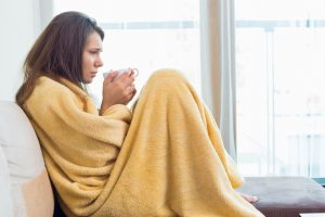 Side view of woman wrapped in a blanket holding a hot drink
