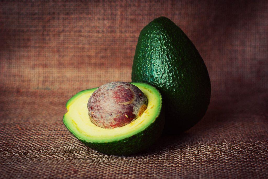 open avocado next to whole avocado