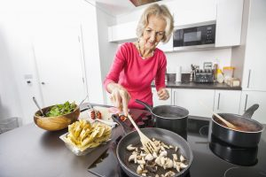 photo of senior woman cooking and practicing kitchen safety