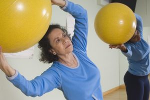 Photo of Senior Woman Using Exercise Ball in Fitness Class