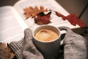 cozy photo of hot drink, book, and fall leaves