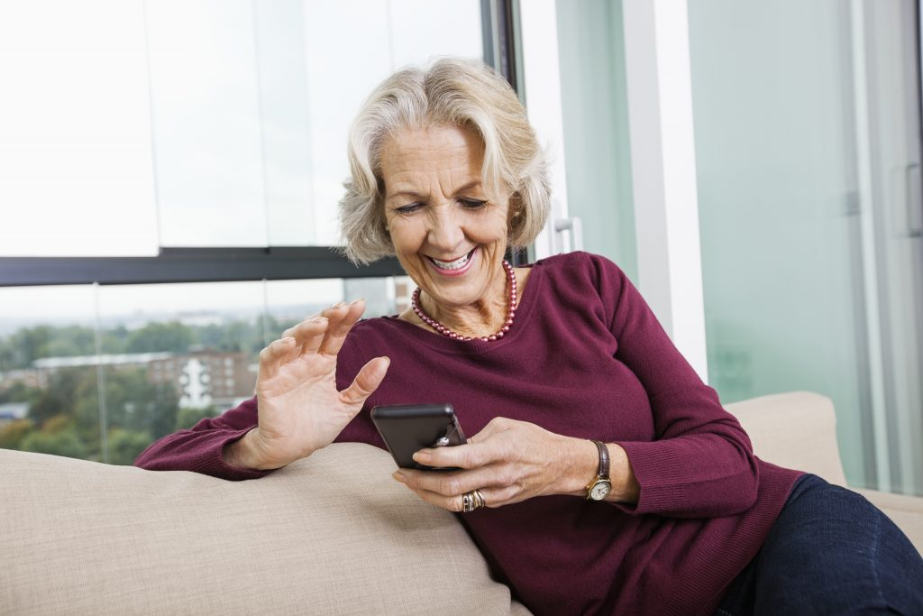 senior woman using mart phone on sofa