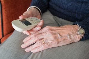 close up of elderly person's hands holding a phone