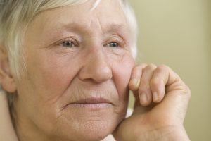 Photo of elderly woman resting her chin on her hand and staring out into the distance with a melancholy look
