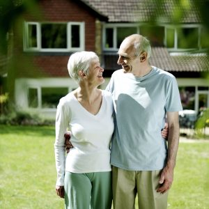photo of senior couple with arms around each other in front of their home