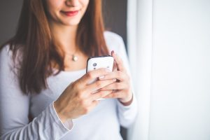 photo of woman using a smartphone