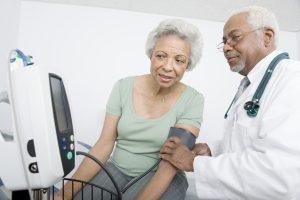 smiling doctor measuring senior woman's blood pressure