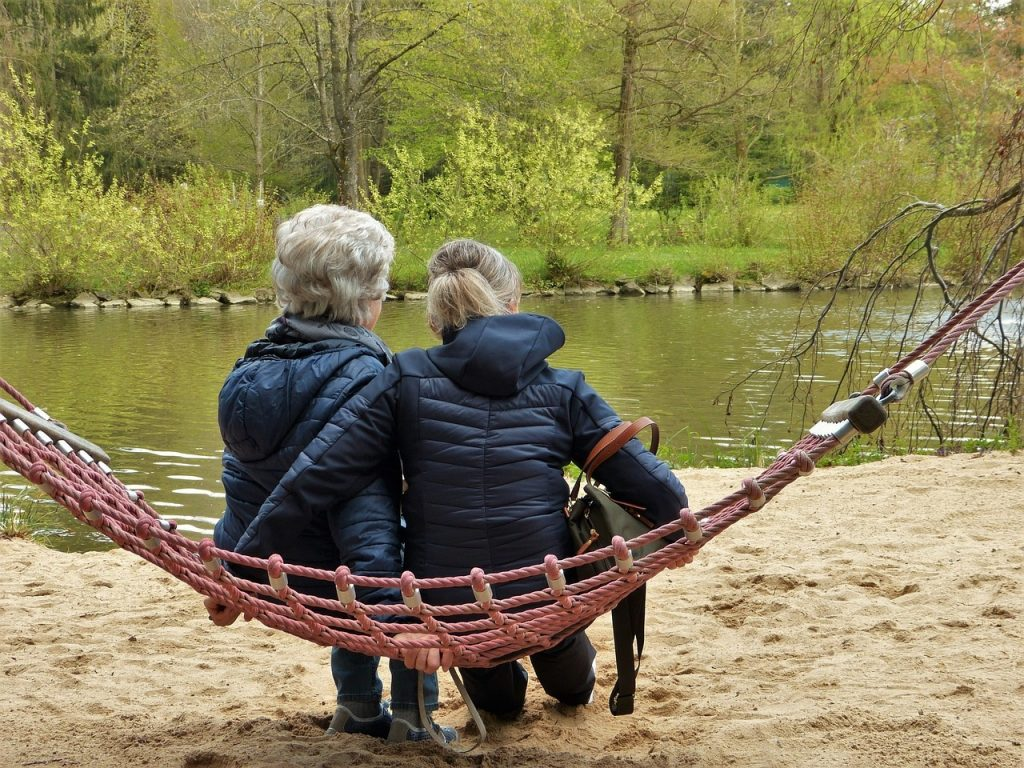 senior women sitting at a lake on a cold winter day