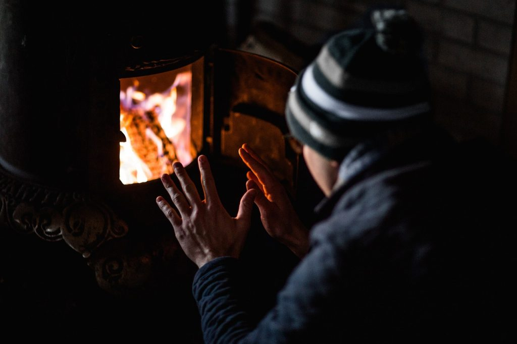 man warming up near fire