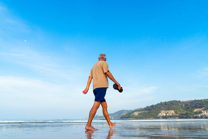 senior man walking along the beach